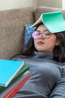Asiatische junge hübsche frau, die auf couch schläft, während stapel bücher auf ihren körper gesetzt