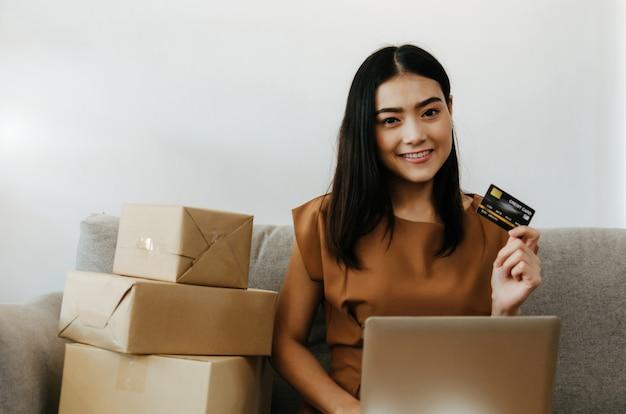 Asiatische junge hübsche frau, die kreditkarte zeigt und mit laptop-computer und verpackungspapppaketkasten für arbeitet, senden dem büro des kunden auftrag zu hause