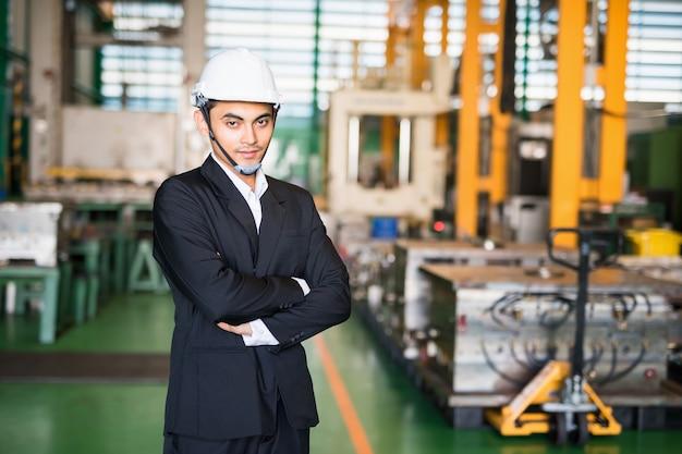 Asiatische junge lagerleiter oder geschäftsinhaber mit bauarbeiterhelm stehen in der fabrik mit maschinen verschwommen abstrakten hintergrund. schwerindustrie und lagerkonzept.