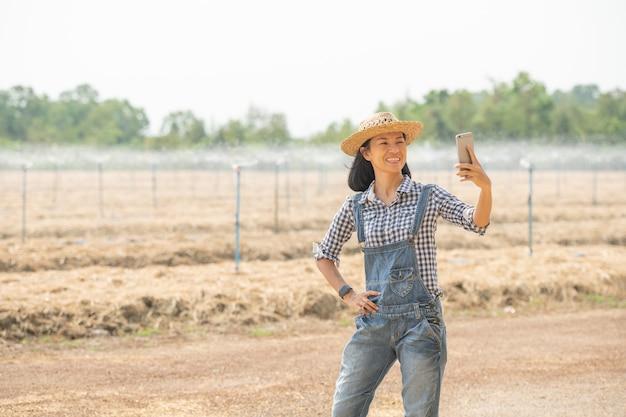 Asiatische junge landwirtin im hut, die in feldfrau steht, die die mobiltelefontechnologie zur inspektion im landwirtschaftlichen garten verwendet. pflanzenwachstum. konzept ökologie, transport, saubere luft, lebensmittel, bioprodukt