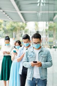 Asiatische junge leute in schutzmasken, die in der warteschlange außerhalb des einkaufszentrums stehen und textnachrichten in smartphones überprüfen