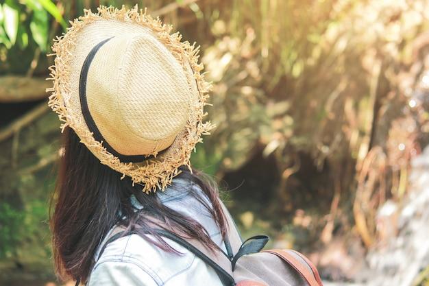 Asiatische junge mädchen mit dem hellen rucksack, der in der natur während der ferien genießt.