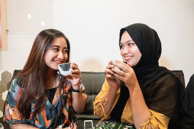 Asiatische junge mädchen plaudern und genießen eine tasse kaffee, während sie in einem café sitzen