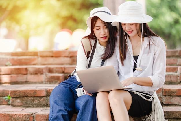 Asiatische junge mädchen und freund-reisender in der stadt, zwei frauen, die gebrauchlaptop sitzen, suchen nach anziehungskräften