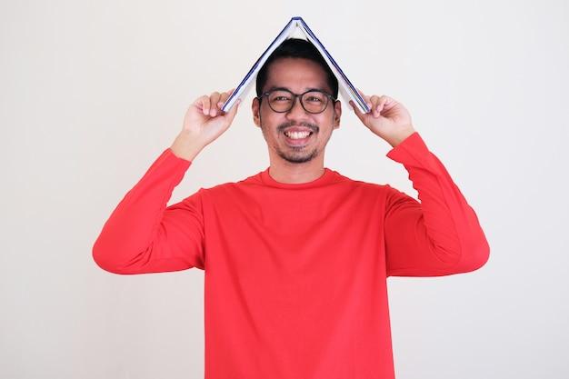 Asiatische junge männer, die glücklich lächeln, während sie ein buch über seinen kopf legen wissenskonzept