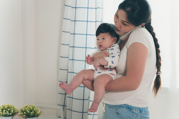 Asiatische junge mutter, die arbeitet und baby hält, während am telefon im heimbüro spricht