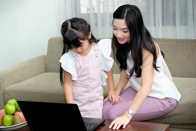 Asiatische junge mutter, die auf sofa im wohnzimmer mit ihrer tochter sitzt, während den gebrauch des laptops unterrichtet