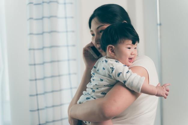 Asiatische junge mutter, die baby bei der unterhaltung am telefon im innenministerium bearbeitet und hält