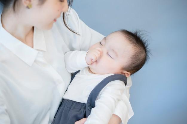 Asiatische junge mutter, die ein schlafendes baby im raum umarmt