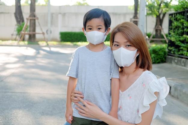 Asiatische junge mutter, die schützende maske pm2.5 für ihren sohn an im freien trägt