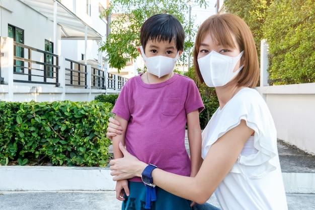 Asiatische junge mutter, die schützende maske pm2.5 für ihren sohn park am im freien trägt