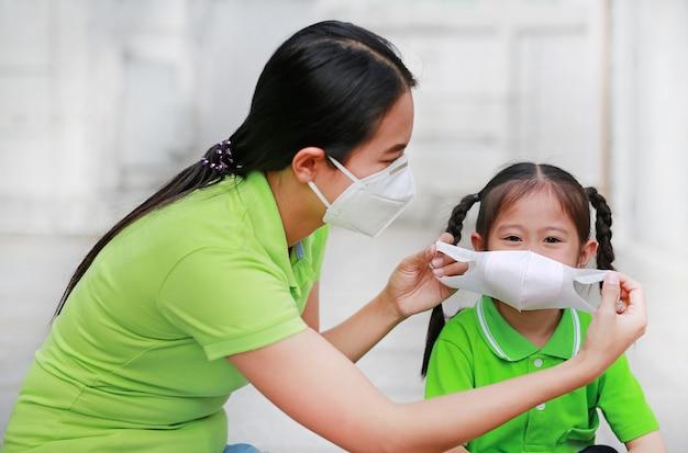 Asiatische junge mutter, die schutzmaske für ihre tochter während draußen zu gegen luftverschmutzung pm 2,5 in bangkok-stadt trägt. thailand.