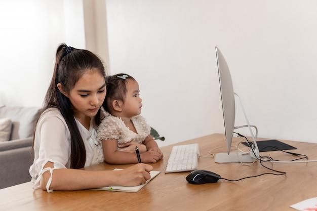 Asiatische junge mutter, die vom haus arbeitet und baby bei der unterhaltung am telefon und der anwendung des computers beim verbringen von zeit mit ihrem baby hält