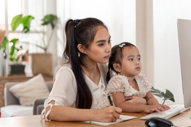 Asiatische junge mutter, die von zu hause aus arbeitet und baby hält, während sie am telefon spricht und computer benutzt, während sie zeit mit ihrem baby verbringt