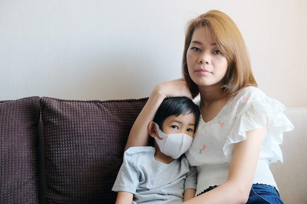 Asiatische junge mutter, die zu hause schutzmaske für ihren sohn trägt