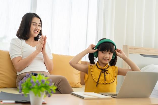 Asiatische junge mutter mit laptop, der kind zu hause unterrichtet