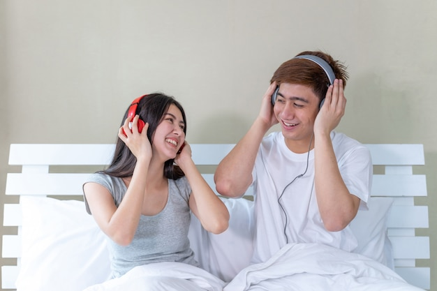 Asiatische junge paare, die auf bett sitzen und kopfhörer zu hörender musik tragen und mit glücklich tanzen