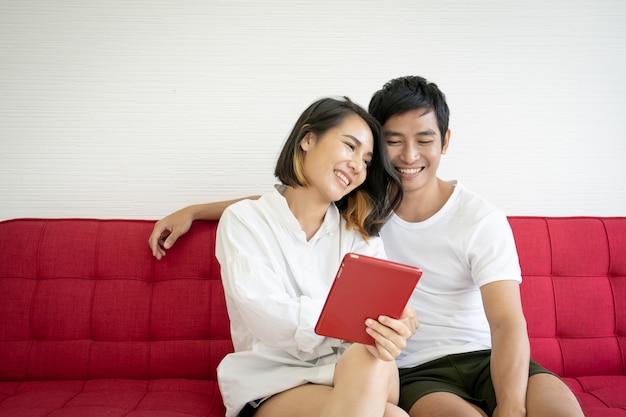 Asiatische junge paare, die auf dem roten sofa im wohnzimmer sitzen und nahes hohes der digitalen tablette verwenden.