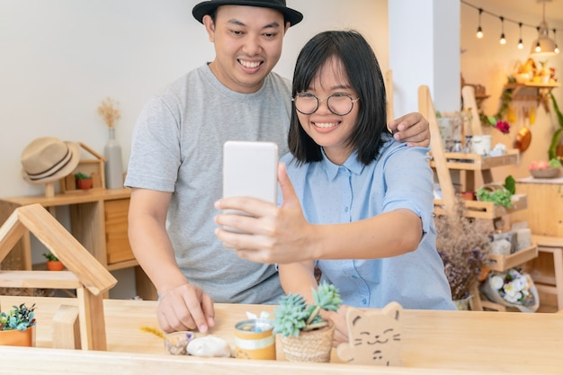 Asiatische junge paare, die das selfie mit glückaktion in der modernen kaffeestube nehmen