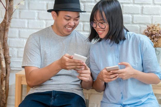 Asiatische junge paare, die den intelligenten handy mit glückaktion sprechen und verwenden