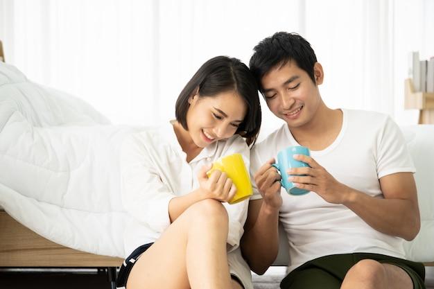 Asiatische junge paare, die morgens zusammen mit kaffee im schlafzimmer genießen