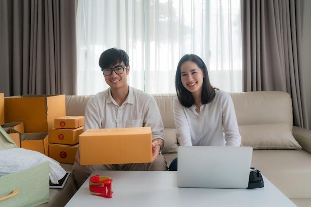 Asiatische junge paare verkaufen online über einen computer und helfen, den kasten im wohnzimmer am haus zu verpacken. kmu-unternehmer oder freiberuflich tätiges unternehmenskonzept