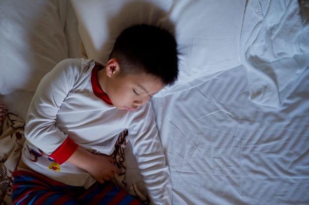 Asiatische junge schlaf auf dem bett, kind krank, kind schlaf