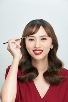 Asiatische junge schöne frau, die kosmetischen puderpinsel auf augenbraue, natürliches make-up, schönheitsgesicht anwendet