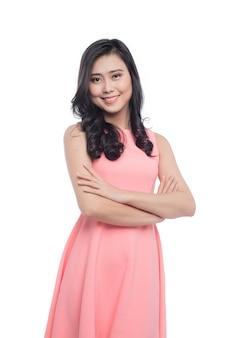 Asiatische junge schöne frau mit dem langen schwarzen haar im rosa kleid, das über weiß steht.