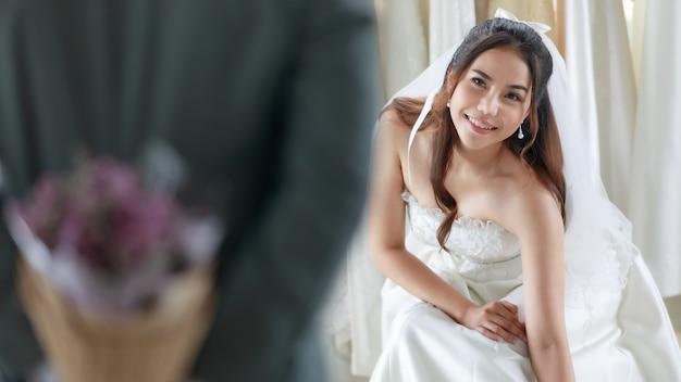 Asiatische junge schöne glückliche lange haarbraut im weißen hochzeitskleid mit durchsichtigem spitzenschleier sitzen lächeln und warten auf den bräutigam im grauen anzug, der blumenstrauß hinter dem rücken versteckt, um in der umkleidekabine zu überraschen.
