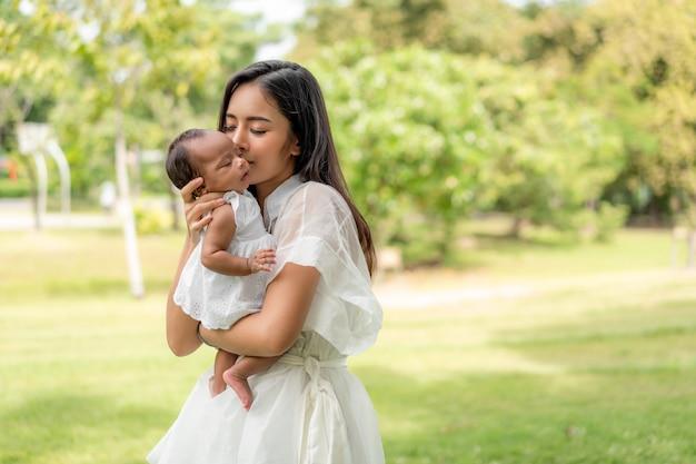 Asiatische junge schöne mutter, die ihr neugeborenes hält, schläft