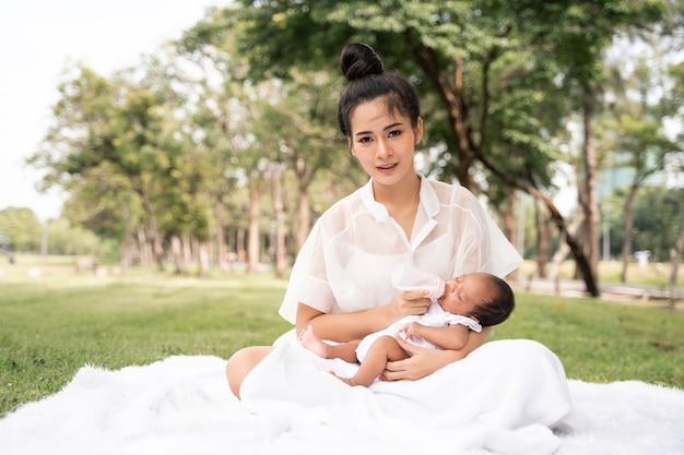 Asiatische junge schöne mutter, die ihr neugeborenes hält