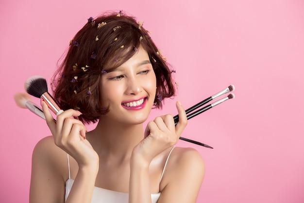 Asiatische junge schönheit des kurzen haares, die kosmetischen puderpinsel aufträgt