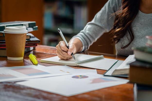 Asiatische junge studentenhandschrifthausarbeit der nahaufnahme in der bibliothek der universität oder des kollegen mit verschiedenem buch und stationär mit kaffeetasse auf holztisch über der buchregalwand, zurück zu schule