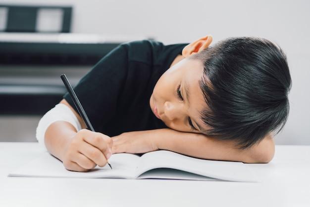 Asiatische jungen an den verletzten händen schreiben ein notizbuch.