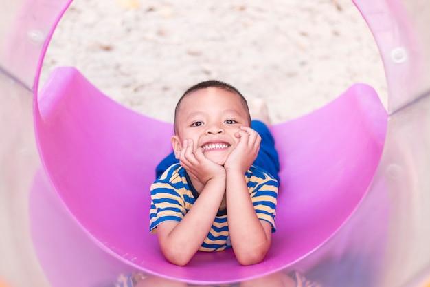 Asiatische jungen, die auf dem spielplatz lächeln