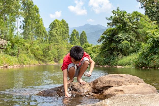 Asiatische jungen füttern den fisch im bach.