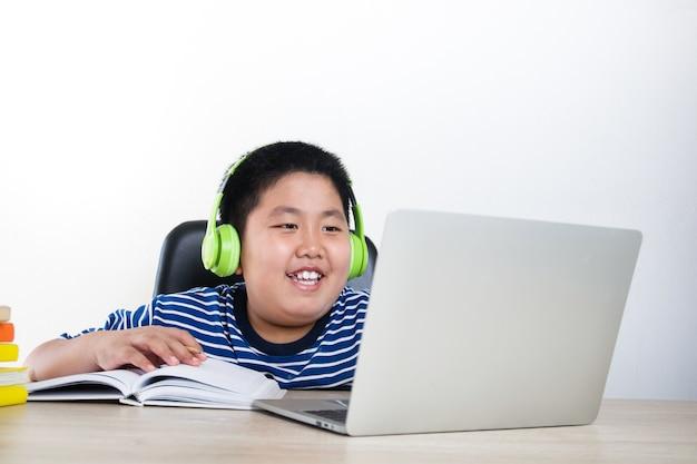 Asiatische jungen lernen online von zu hause aus per videoanruf. verwenden sie einen laptop, um mit lehrern zu kommunizieren. bildungskonzept, soziale distanzierung zur verringerung der ausbreitung des coronavirus (covid-19)