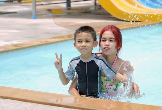 Asiatische jungen und mädchen saßen im pool und lächelten glücklich.