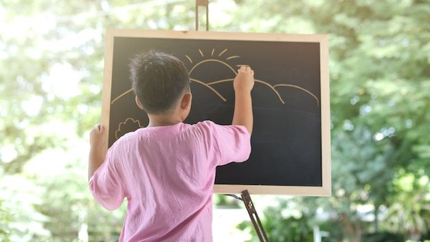 Asiatische jungenleute, die kreativ sind und den berg mit der sonne zeichnen