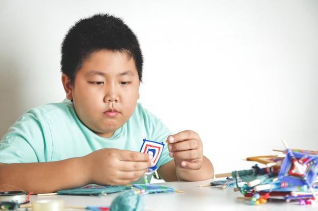 Asiatische jungs sitzen da, um mit ihren eigenen händen spielzeug herzustellen. weißer hintergrund