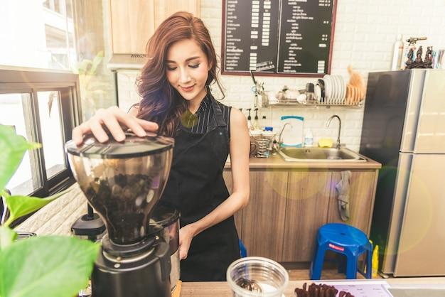 Asiatische kaffeemaschinefrau, die kaffee in der kaffeestube macht