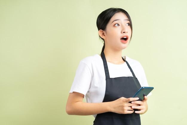 Asiatische kellnerin, die das telefon mit einem überraschten gesicht hält