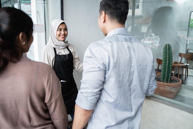 Asiatische kellnerin laden gäste ein, einzutreten