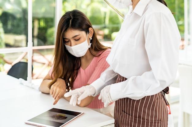 Asiatische kellnerin tragen gesichtsmaske und gesichtsschutz mit tablette, um das elektronische menü des restaurants zu zeigen