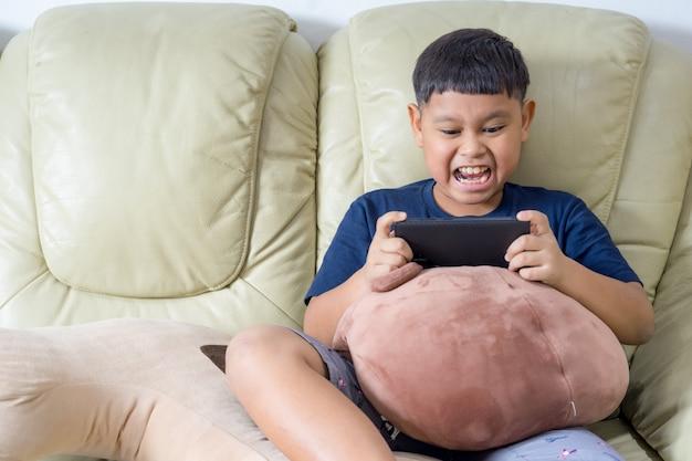 Asiatische kinder, die auf dem sofa sitzen, nehmen es ernst, spiele auf dem handy zu spielen