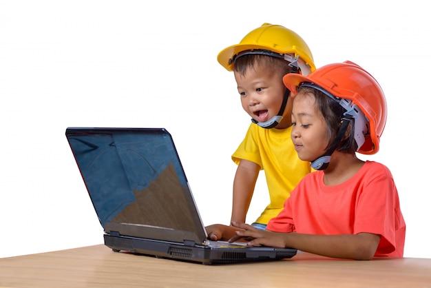 Asiatische kinder, die den schutzhelm tragen und den hobel lokalisiert auf weiß denken
