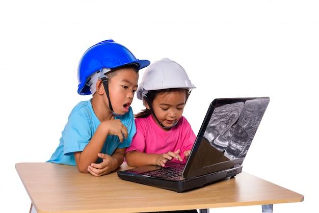 Asiatische kinder, die den schutzhelm tragen und hobel lokalisiert auf weißem hintergrund denken. kinder und bildungskonzept