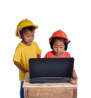 Asiatische kinder, die den schutzhelm tragen und hobel lokalisiert auf weißem hintergrund denken.