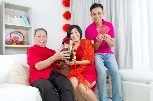 Asiatische kinder, die geschenkkorb und rotes paket dem elternteil auf chinesischem neuem jahr darstellen